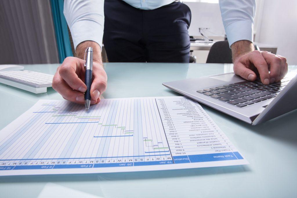 Businessperson's Hand Working On Gantt Chart Using Laptop